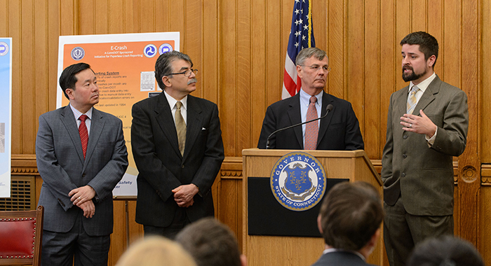 Eric Jackson, assistant research professor, right, speaks at a press conference held at the state capitol to announce formation of the Connecticut Transportation Safety Research Center on April 29, 2013. From left are Provost Mun Choi, Kazem Kazerounian, interim dean of engineering, and James P. Redeker, commissioner of ConnDOT. (Peter Morenus/UConn Photo)