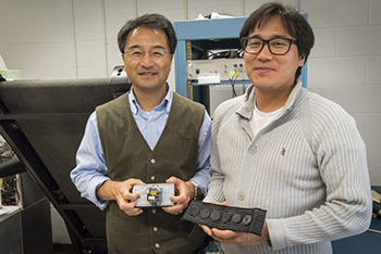 At left Ki Chon, department chair of biomedical engineering, and graduate assistant Yeon Noh, are developing a device for early detection of an irregular heartbeat. (Sean Flynn/UConn Photo)