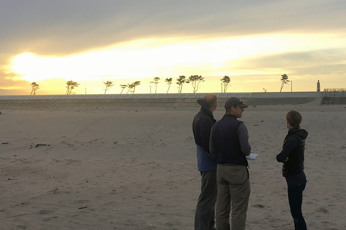 UConn professors on the beach near Sendai, in northeastern Japan, surveying the damage left by the tsunami of 2011. Note the recently raised sea wall, and trees with healthy branches indicating the height of the 2011 tsunami wave. (Photo courtesy of William Ouimet)