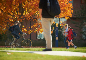Students walk and ride bicycles past fall foliage along the Student Union Mall on Oct. 20, 2015. (Peter Morenus/UConn Photo)