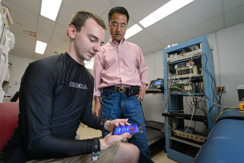 Cameron Flower, a biomedical engineering student demonstrates an ECG sensor and smartphone health sensor with Ki Chon, chair of biomedical engineering on April 22, 2016. (Peter Morenus/UConn Photo)
