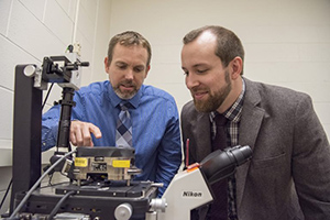 UConn engineering professor Bryan Huey, left, and post-doc Justin Luria prepare a specimen for study under a customized Atomic Force Microscope (AFM) in UConn's Institute of Materials Science. Huey and Luria were part of a team that developed a breakthrough materials mapping technique that can be used to produce unique 3-D images of materials at the nanoscale. (Ryan Glista/UConn Photo)
