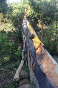 A makeshift aqueduct, constructed by the villagers using plastic tarps, sheet metal, and sticks. The inventive structure is subject to leakage.