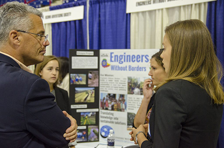 From left, Jennifer Skoog '19 (ENG), Megan Leether '17 (ENG), and Georgina Talbot '17 (ENG), speak with business leaders about the student organization Engineers Without Borders during the Career Fair at Gampel Pavilion on Oct. 5. (Garrett Spahn '18 (CLAS)/UConn Photo)